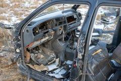 Wrak van een verwoeste auto op een weide Gedemonteerd autoskelet royalty-vrije stock afbeelding