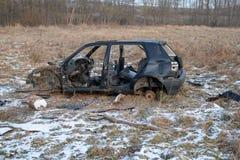 Wrak van een verwoeste auto op een weide Gedemonteerd autoskelet royalty-vrije stock afbeeldingen