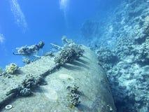 Wrak van oud die schip met koraalrif bij de bodem van tropische overzees, onderwaterlandcape wordt behandeld stock foto's