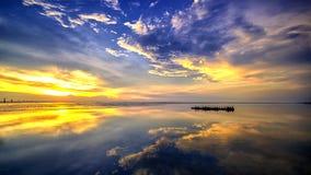 Wrakboot tijdens zonsondergang bij strand stock fotografie
