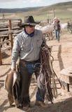 Wrangler del cowboy che porta il suoi hackamore, coperta di cavallo, corda del cavo e sella alla stanza di puntina fotografia stock libera da diritti