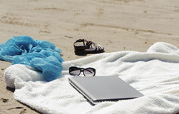 Wrap, laptop, scarf and mules on the beach Royalty Free Stock Image