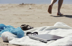 Wrap, laptop, scarf and mules on the beach Royalty Free Stock Photos