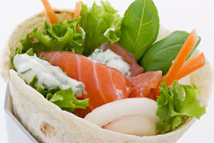 Wrap with Salmon. Wrap with fresh smoked salmon, salad and vegetables as closeup on white background Stock Images