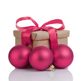 Wraped gift box with purple bow, christmas balls Royalty Free Stock Photo