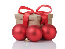 Wraped gift box with red bow and christmas balls Royalty Free Stock Image
