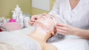 wraping在影片客户的面颊的美容师做osmetic做法清洗在整容术诊所的面孔 股票视频