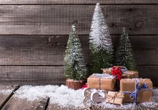 Wrapped boxes on decorative sled, red berries and fir trees on royalty free stock photos