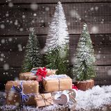 Wrapped boxes on decorative sled, red berries and fir trees on royalty free stock images