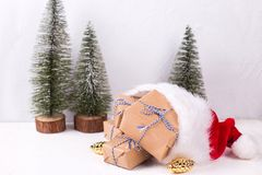 Wrapped boxes with presents, decorative golden pine cones in Santa hat and fir trees on white textured background stock image