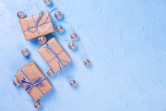 Wrapped boxes with presents and silver fairy lights on blue textured background. Top view stock images