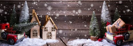 Wrapped boxes in red car, decorative houses and fir trees on ag stock images
