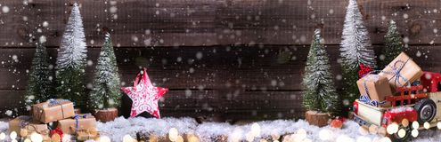 Wrapped boxes, red decorative star and fur trees on aged wooden royalty free stock images