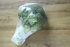 Wrapped Broccoli. A plastic foil wrapped piece of fresh Broccoli stock image
