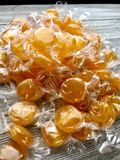 Wrapped butterscotch candies. Wrapped butterscotch hard candies on a wood surface stock photo