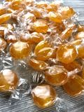 Wrapped butterscotch candies. Wrapped butterscotch hard candies on a wood surface royalty free stock image