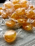 Wrapped butterscotch candies. Wrapped butterscotch hard candies on a wood surface stock photography
