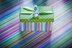 Wrapped cardboard box with present on striped tablecloth celebra Royalty Free Stock Image