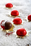 Wrapped Christmas chocolate balls on icing sugar Stock Image