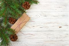 Wrapped Christmas gifts on dark rustic wooden table with pine cones and fir branches. With copy space for your text stock photo