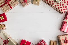 Wrapped Christmas gifts. On a white wooden background, overhead view