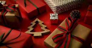 Wrapped christmas gifts and wooden fir tree decoration on red background. Dolly shot stock video