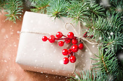 Wrapped christmas presents, fur tree branches, red berries on rustic wooden background. Drawn snow effect. Stock Photos