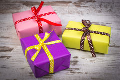 Wrapped colorful gifts for Christmas or other celebration on old white plank Royalty Free Stock Photo