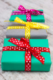 Wrapped colorful gifts for Christmas or other celebration on old white plank Stock Photography