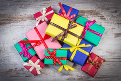 Wrapped colorful gifts for Christmas or other celebration on old white plank Stock Photos