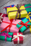 Wrapped colorful gifts for Christmas or other celebration on old white plank Stock Images