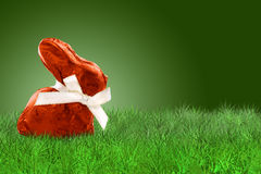 Wrapped Easter bunny on grass. Wrapped Easter bunny with red aluminium on grass on grass on green background Stock Photos
