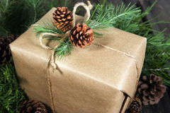 Wrapped Gift. Gift wrapped in plain brown kraft paper,  tied with natural jute string and adorned with fresh pine sprigs and pine cones Royalty Free Stock Photo