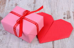 Wrapped gift for birthday, valentine or other celebration and red heart Royalty Free Stock Photo