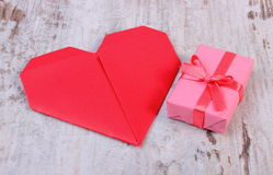 Wrapped gift for birthday, valentine or other celebration and red heart Stock Images