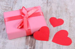 Wrapped gift for birthday, valentine or other celebration and red hearts Stock Photo