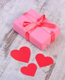 Wrapped gift for birthday, valentine or other celebration and red hearts Royalty Free Stock Images