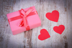 Wrapped gift for birthday, valentine or other celebration and red hearts Royalty Free Stock Photos