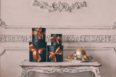 Wrapped gift black boxes with ribbons as Christmas presents on a table luxury white wall design bas-relief stucco. Wrapped gift black boxes with ribbons as Royalty Free Stock Photography