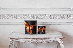 Wrapped gift black boxes with ribbons as Christmas presents on a table luxury white wall design bas-relief stucco Stock Photography