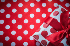Wrapped gift box with bow on polka-dot red table cloth holidays Stock Photography
