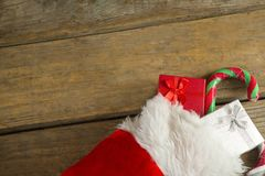 Wrapped gift box and candy cane in stocking against wooden wall Stock Images