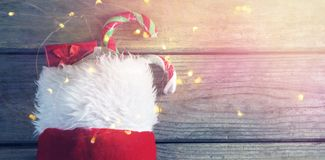Wrapped gift box and candy cane in stocking against wooden wall. During christmas time Royalty Free Stock Photo