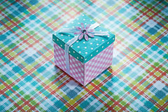 Wrapped gift box on checked fabric background celebrations conce Royalty Free Stock Photo