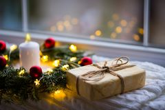 Wrapped gift box near fir wreath decorated with red Christmas balls, white burning candle and coiled with glowing garland with war. M light near window in stock image