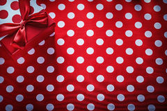 Wrapped gift box on polka-dot red tablecloth holidays concept Stock Photos