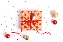 Wrapped gift box with red ribbon and bow on white wooden background. royalty free stock image