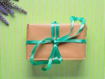 Wrapped gift box. Spring holidays present. Wrapped gift box with green ribbon. Spring holidays easter present. Top view Stock Images
