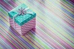 Wrapped gift box on stripy fabric background celebrations concep Stock Photography