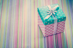 Wrapped gift box on stripy fabric background holidays concept Royalty Free Stock Photo